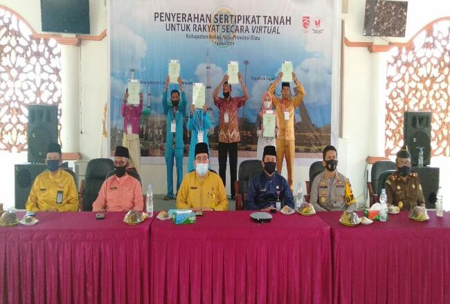 Bupati Sukiman secara simbolis, menyerahkan sertipikat tanah melalui program Tora ke warga, didampingi Kepala ATR/BPN Rohul dan pejabat Forkpinda, di pendopo rumah dinas Bupati.