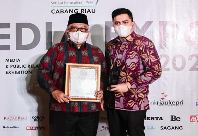 Asisten III, H Khairil Adli didampingi Kabid IKP Diskominfo Dumai Muhammad Sadam menerima penghargaan dari SPS Riau.