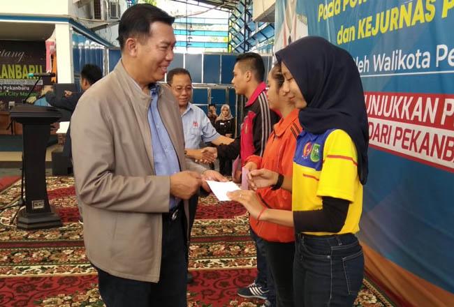 Walikota Pekanbaru, Dr Firdaus MT di dampingi Ketua Umum KONI Riau menyalami, dan menyerahkan tambahan uang saku atlet secara simbolis, Senin (28/10/2019).