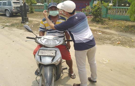 Tampak Wakil Ketua DPRD Kabupaten Inhu Masyrullah SP saat membagikan masker kepada pengguna jalan.