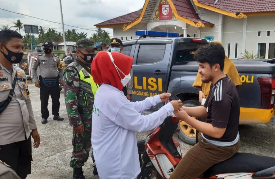 Petugas saat memakaikan masker kepada warga yang akan masuk ke wilayah RT yang diberlakukan PPKM skala mikro