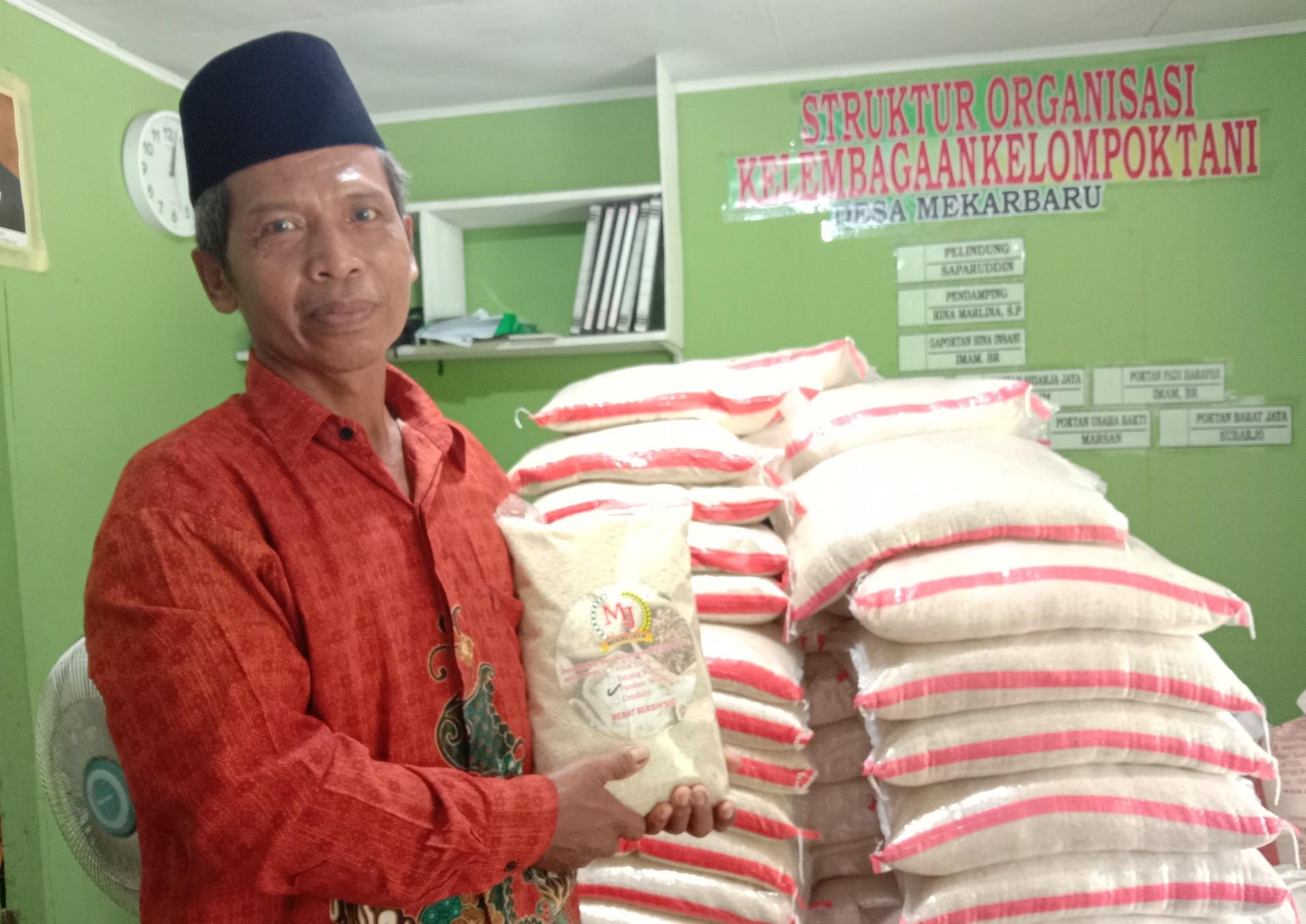 Direktur BumDes Mekar Jaya, Desa Mekar Baru Imam BR, saat memperlihatkan beras jenis Pandan Wangi hasil produksi BumDes
