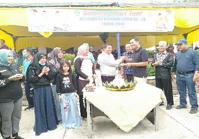 Sekda Abdul Haris, berikan nasi tumpeng ke Camat Rambah Samo Adi Irawan saat rayakan hari jadi Kecamatan Rabah samo ke 24 yang berlangsung meriah.
