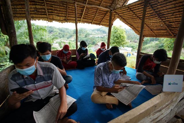 Para pelajar di Desa Telaga Said, Kecamatan Sei Lepan, Kabupaten Langkat, Sumatera Utara sedang mengikuti pembelajaran jarak jauh (PJJ) secara daring di sebuah balai yang terletak di atas sebuah bukit, Senin (3/8/2020).