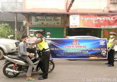Satlantas Polres Rohil membagikan masker pada pengendara yang lewat.