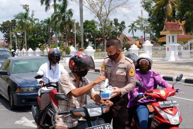 Pembagian masker oleh Taruna Akademi Kepolisian asal Riau, dalam memperingati Sumpah Pemuda.