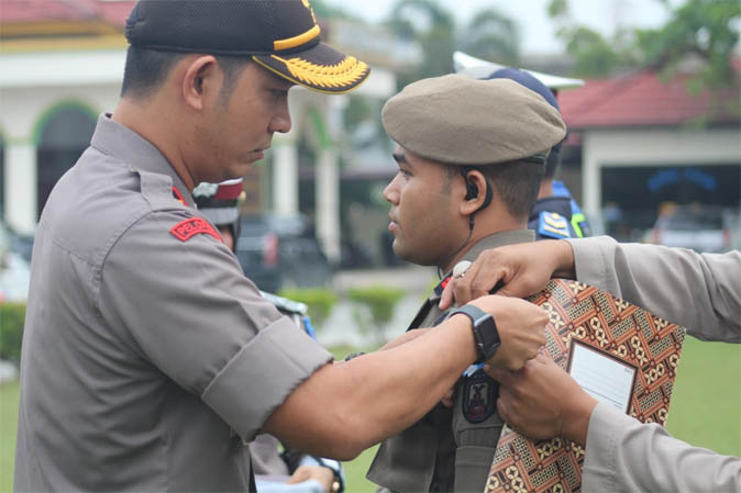 Wakapolres Pelalawan Kompol Rezi Darmawan,S.Ik,M.Ik memasang pita kepada personel menandai pelaksanaan Operasi Zebra Siak 2019 di Mapolres Pelalawan, Rabu (23/10/2019).