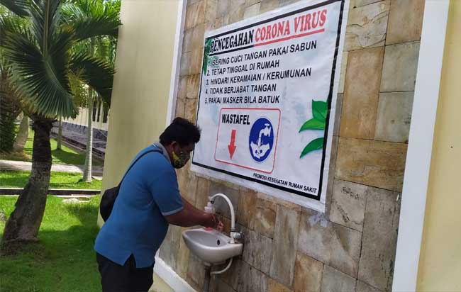 Salah seorang wartawan di Kepulauan Meranti tetap melakukan penerapan protokol kesehatan saat akan meliput,mencuci tangan dan memakai masker