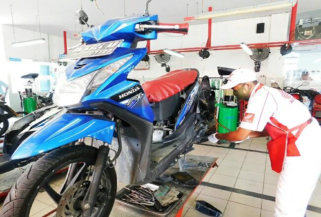 Mekanik service motor Honda milik konsumen menggunakan masker dan sarung tangan.