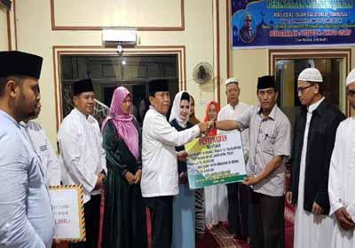 Bupati Sukiman didampingi Sekda Abdul Haris, serahkan bantuan untuk anak yatim dari BAZNas Rohul ke pengurus masjid, saat Safari Ramadan di Kecamatan Tambusai.