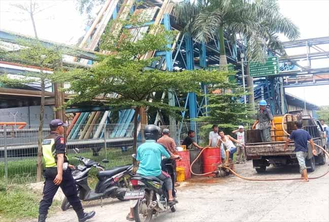 Para pekerja PT Ivo Mas Tunggal Dumai tampak membersihkan tumpahan CPO  secara manual maupun dengan disedot.