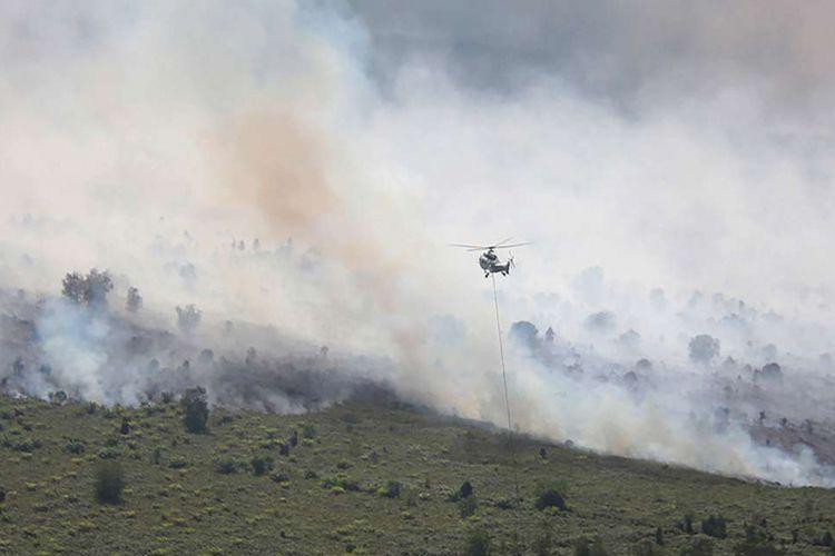 Sebuah helikopter Super Puma AS332L1 milik APP Sinar Mas Forestry bersiap melakukan pengeboman air (water bombing) terhadap hutan dan lahan perkebunan sawit rakyat yang terbakar di Desa Gurun Panjang di Dumai, Dumai, Riau, Senin (25/2/2019).