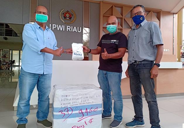 Dinas ESDM Provinsi Riau diwakili salah seorang wartawan, Budy menyerahkan bantuan masker untuk PWI Riau yang diterima Sekretaris PWI Riau, Amril Jambak, Rabu (13/1/2021). Foto IST