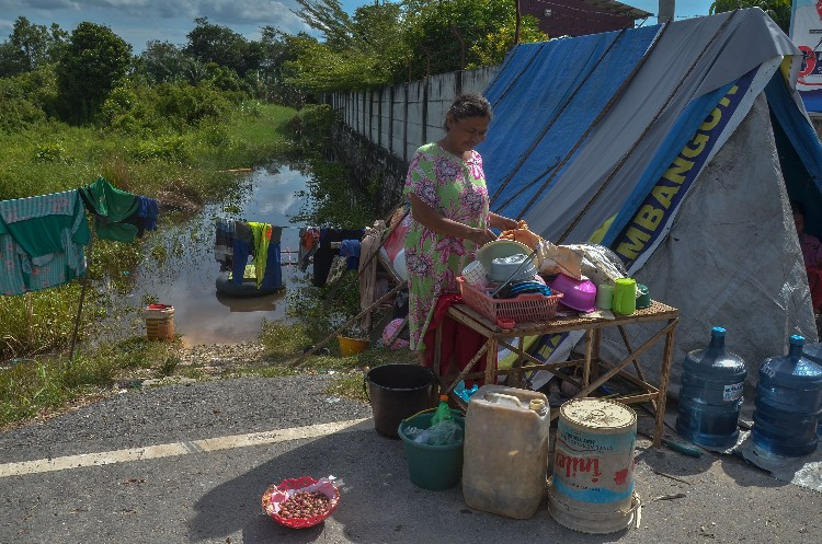 Sejumlah warga korban banjir berada di tenda darurat di pinggir Jalan Nelayan Ujung, Kecamatan Rumbai, Pekanbaru, Riau, Minggu (25/11/2018). Memasuki hari keenam sebagian warga korban banjir masih bertahan di tempat pengungsian pinggir jalan dengan mendirikan tenda dan dapur darurat. FOTO: Wahyudi