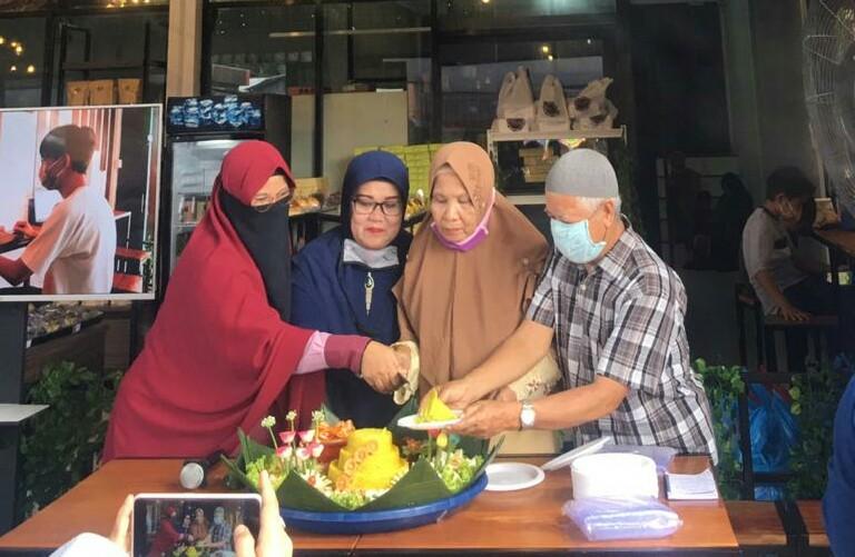 Pemotongan tumpeng sebagai syukuran atas dibukanya Outlet Makacha di Jalan Inpres, Pekanbaru.