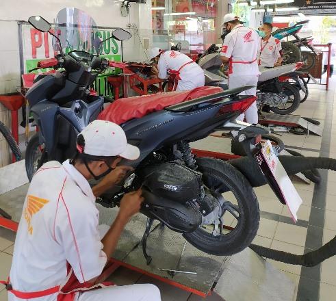 Petugas mekanik sedang melakukans service sepeda motor Honda di AHASS.