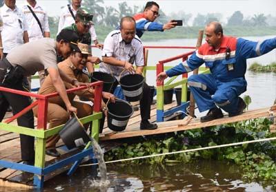 GM Pertamina RU II M. Dharmariza, bersama Wakil Bupati Rohil Jamiluddin tebar 10.000 Benih Ikan Patin di Sungai Rokan.