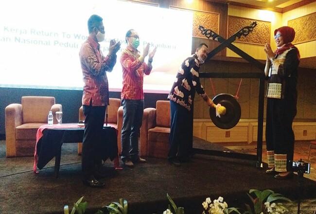 Kepala Dinas Tenaga Kerja dan Transmigrasi Provinsi Riau H Jonli SSos MSi memukul gong saat meresmikan program Pusat Layanan JKK-RTW di Hotel Pangeran, Pekanbaru, Kamis (13/8/2020). Foto: Riaupos