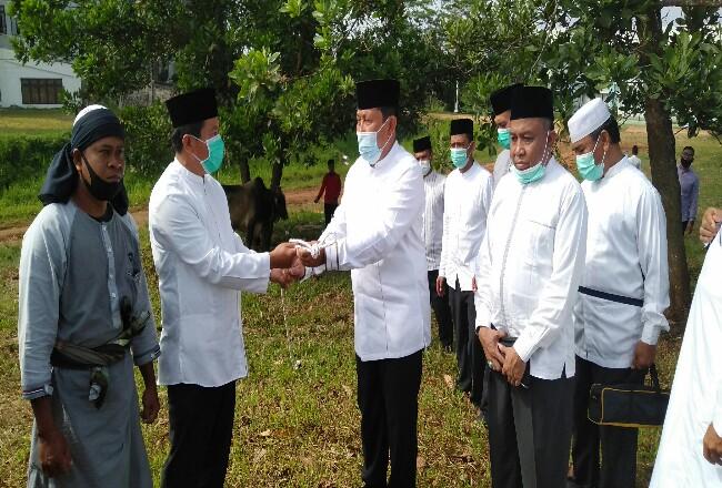 Bupati Sukiman, serahkan hewan kurban kepada Ketua Umum Pengelola Masjid Agung Islamic Centre Rohul H Abdul Haris saat memantau pelaksanaan penyembelihan sapi kurban di kawasan Masjid Agung.