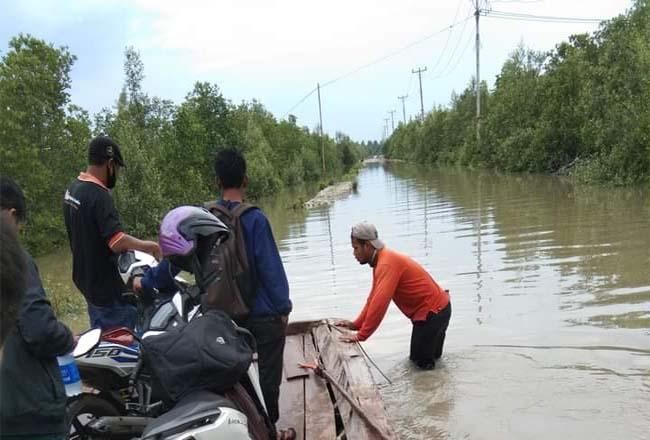 warga di Meranti terpaksa merogoh saku lebih dalam untuk menyeberang saat banjir rob.
