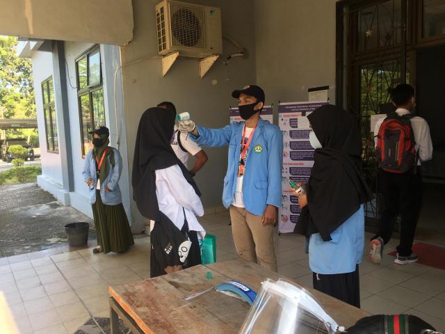 Mahasiswa yang tergabung dalam Satgas Kerelawanan Covid-19 Universitas Riau ikut membantu jalannya pelaksanaan UTBK 2020.