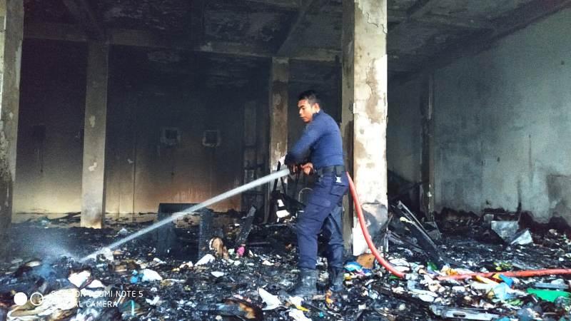 Salah seorang petugas Damkar tengah memadamkan api di gudang arsip milik Pemkab Kuansing yang terbakar.