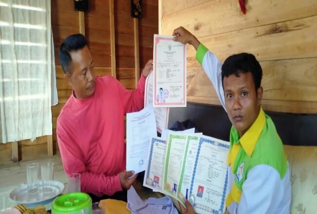 Jefrizal selaku juru bicara (jubir) Kepala Desa Mengkopot saat menunjukkan dokumen ijazah asli milik Kepala Desa.