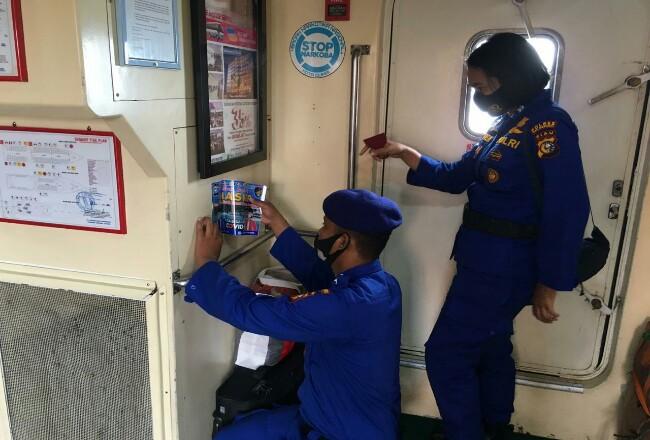 Petugas memasang stiker imbauan pakai masker di kapal.