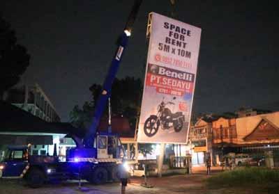 Satpol PP Kota Pekanbaru memotong tiang reklame di halaman Kantor Meteorologi Pekanbaru.
