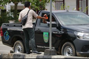 Petugas BPBD Rohul bagikan ke pengendara di simpang lampu merah Taman Kota Pasir Pangaraian, dimana BPBD bagikan 1000 helai masker gratis untuk warga tidak meluasnya penyebaran Covid-19 di Rohul.