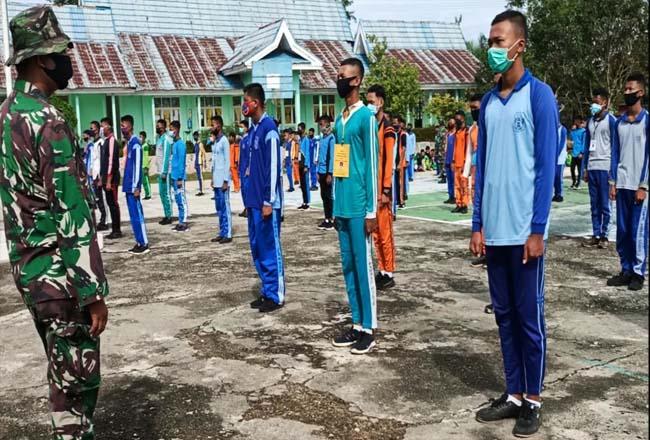 Instruktur dari Babinsa Koramil 02/Rambah, beri pelatihan PBB dan tata upacara saat ikuti PLS kepada pelajar baru Kelas X SMKN I Rambah dengan tetap berlakukan protokoler kesehatan.