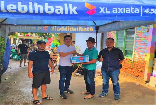 Region Group Head XL Axiata Regional Jabodetabek dan Kalimantan, Francky Rinaldo Pakpahan (kedua kiri) menyerahkan bantuan darurat berupa barang-barang kebutuhan pokok sehari-hari secara langsung kepada korban banjir di Kebon Pala, Jatinegara, Jakarta Timur.