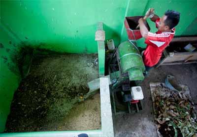 Warga sedang memanfaatkan komposter di bank sampah untuk mengubah sampah rumah tangga menjadi pupuk organik.