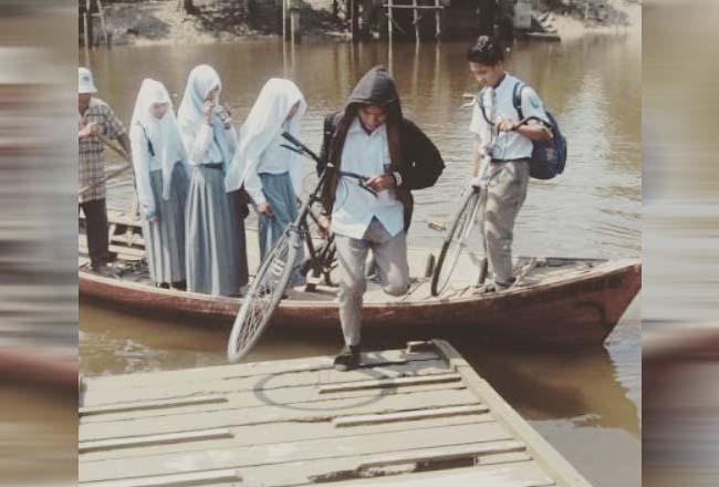 Siswa menyeberangi sungai dengan sampan untuk pergi ke sekolah.