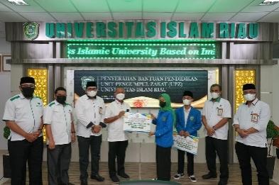 Suasana penyerahan bantuan pendidikan dari Unit Pengumpul Zakat UIR kepada dua perwakilan mahasiswa di Gedung Rektorat UIR Pekanbaru.