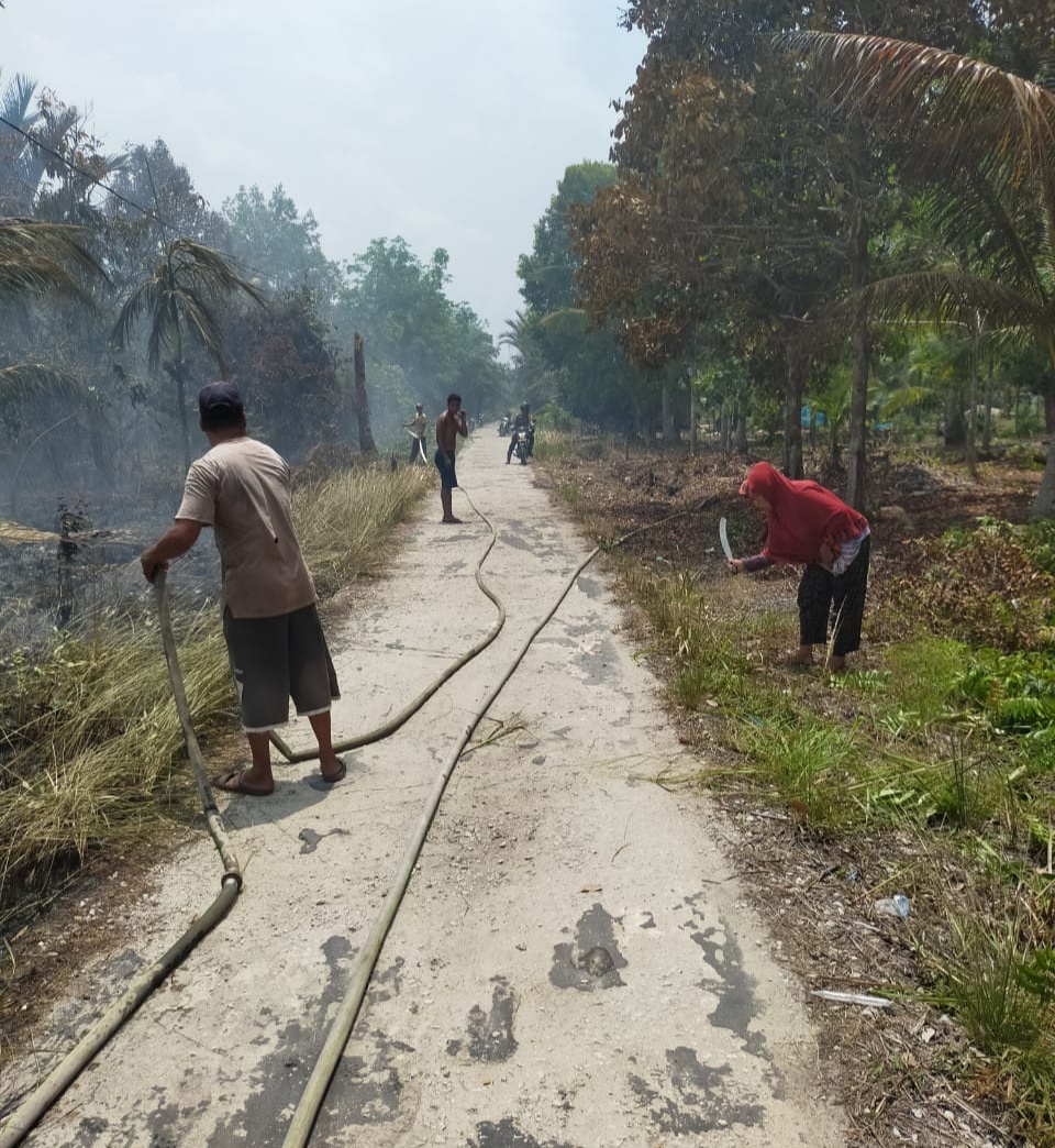 Karhutla di Tanjung Peranap sudah mendekati tepi jalan, terlihat beberapa warga berusaha memadamkan api dengan alat seadanya