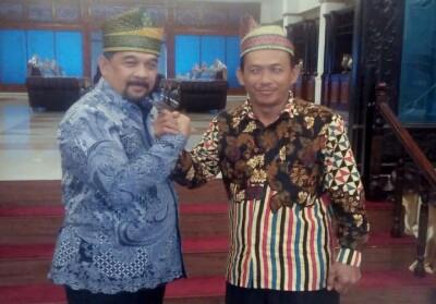 Wagubri H Edi Natar Nst, berbincang dengan Kades Sialang Jaya Yuherman Daulay sambil mengenakan tanjak Unak Serantau khas Rohul.