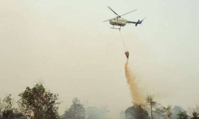 Helikopter Bolkow BO-105 dari Badan Nasional Penanggulangan Bencana (BNPB) melakukan water bombing di atas lahan gambut yang terbakar, di perkebunan sawit di Kecamatan Terentang, Kabupaten Kubu Raya, Kalbar, Rabu (21/10).  FOTO: Antara
