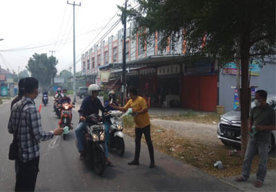 Anggota Cymot saat bagikan ribuan masker ke warga yang melintas.