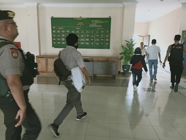 Penyidik KPK keluar dari ruangan pengadaan barang dan jasa di kawal personel Polres Dumai.