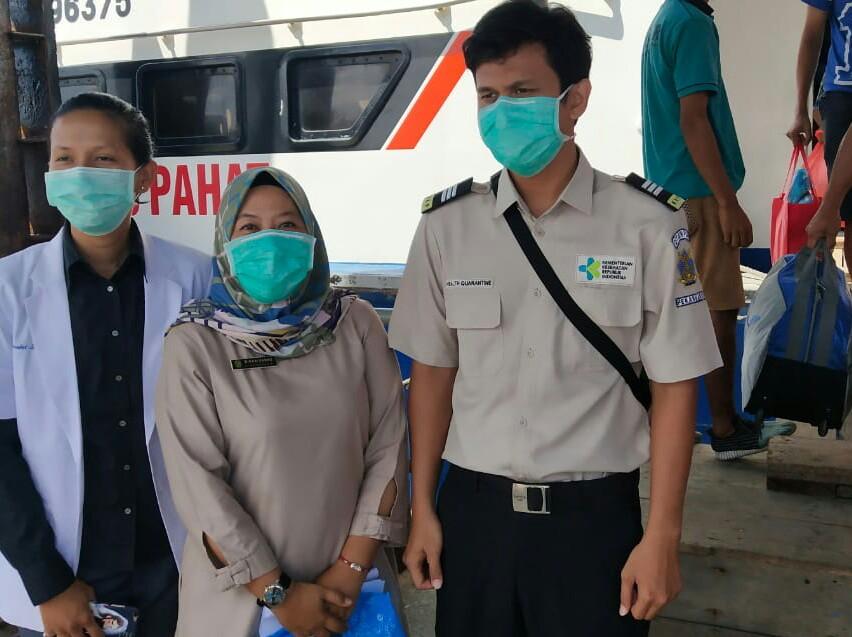 Petugas yang melakukan pengecekan kesehatan penumpang dari Malaysia di Pelabuhan Tanjung Harapan, Selatpanjang.