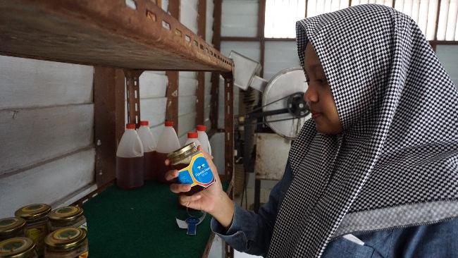 Seorang warga sedang memeriksa madu Foresbi yang akan dibelinya di Community Development (CD) PT Riau Andalan Pulp and Paper (RAPP).