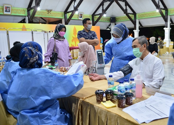 Gubernur Riau (Gubri) Syamsuar dan istrinya, Misnarni telah menerima suntikan vaksin Covid-19 tahap kedua untuk meningkatkan imunitas tubuh di Balai Pauh Janggi, Kamis (29/4/2021) malam.