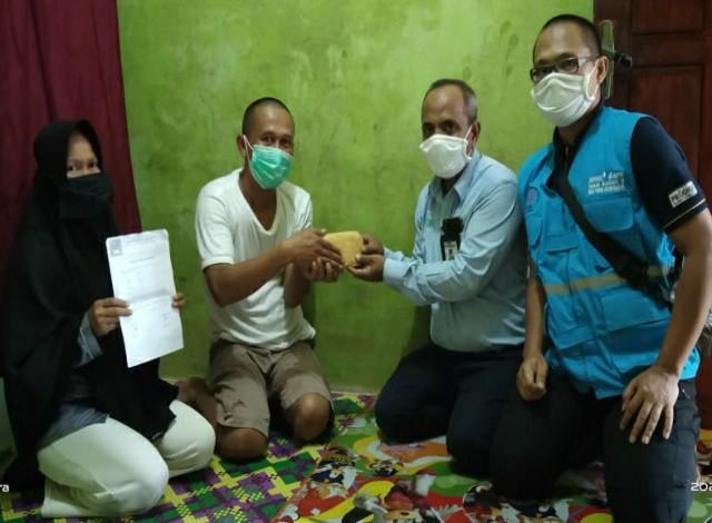 Pembina STM Riau Kompleks PT RAPP, Ishak, menyalurkan bantuan pada Dodi, yang istrinya terkena kanker serviks. Foto Andy