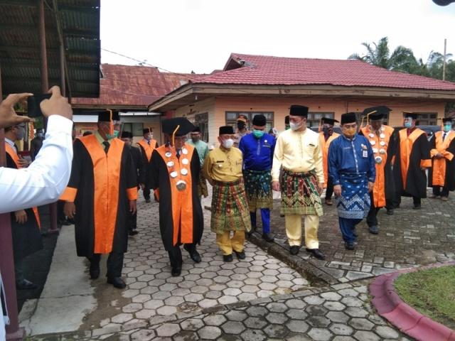 Bupati Pelalawan HM Harris didampingi anggota DPR RI DR. Syahrul Aidi bersama Direktur Politehnik Padang tengah berbincang sambil berjalan menuju aula tempat pelaksanaan wisuda.