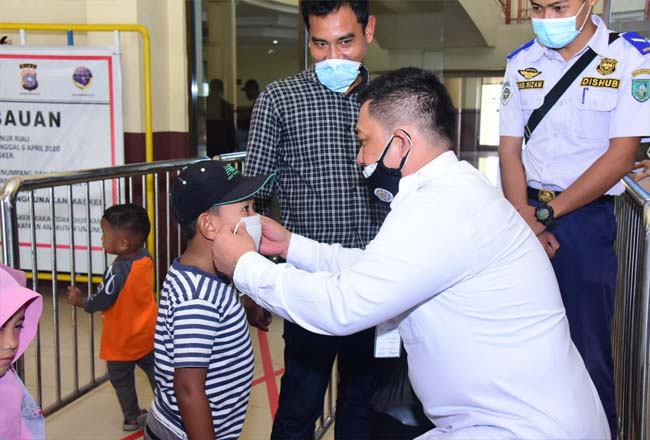 Pj Bupati Bengkalis Syahrial Abdi memakaikan masker kepada seorang anak yang tidak memakai masker saat berada di pasar.