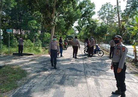 Petugas Polsek Bantan berjaga-jaga di jalan masuk lokasi wisata pantai Selatbaru. FOTO: Reskrim Polsek Bantan