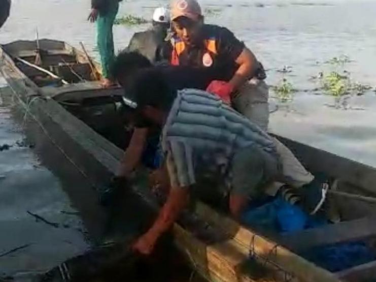 Tampak petugas saat mengevakuasi jasad korban ke atas sampan.