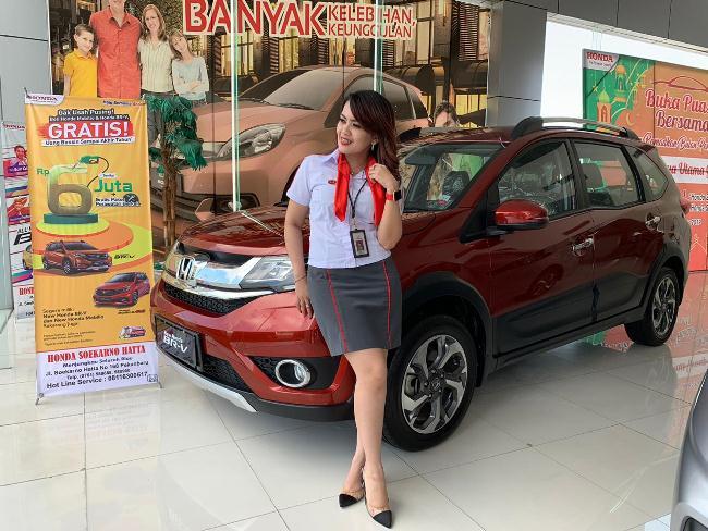 Seorang sales counter berfoto di depan Honda BR-V di showroom HSH Pekanbaru