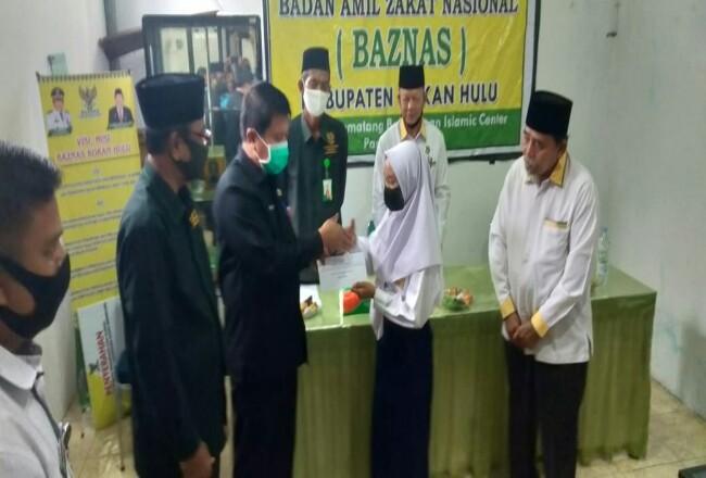 Sekda Rohul H Abdul Haris, serahkan secara simbolis bantuan dana pendidikan bagi pelajar kurang mampu di Rohul, disakskan Ketua BAZNas Rohul Armen ZA dan komisioner BAZNas lainnya.